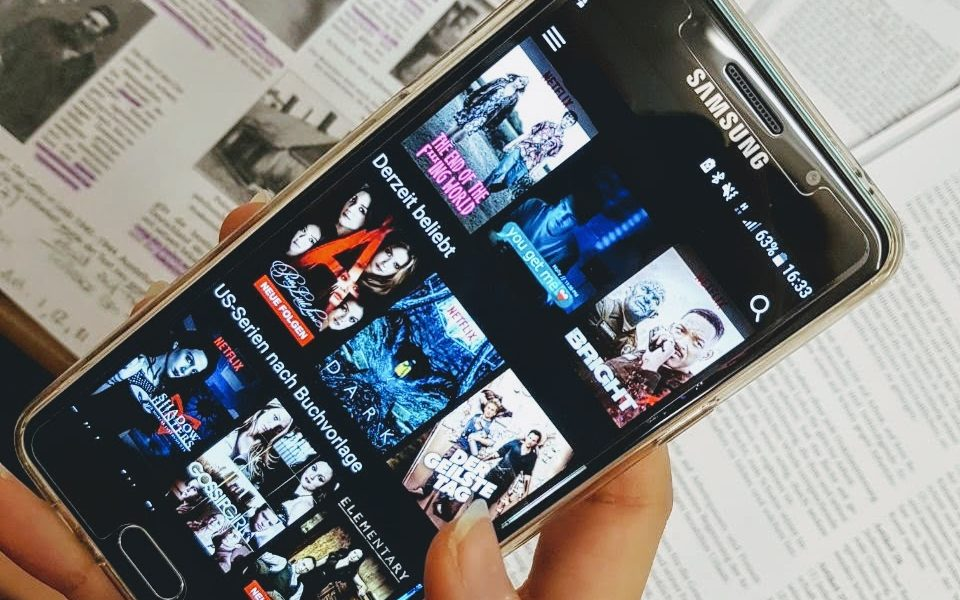 Handy mit Netflix offen, im Hintergrund Arbeitsblätter