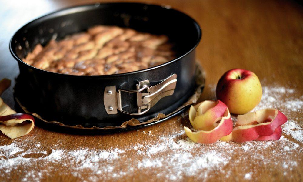 Auf dem Bild sieht man einen Kuchen in einer Kuchenspringform, vor welchem Äpfel liegen und auf der Tischplatte Mehl verstreut ist.
