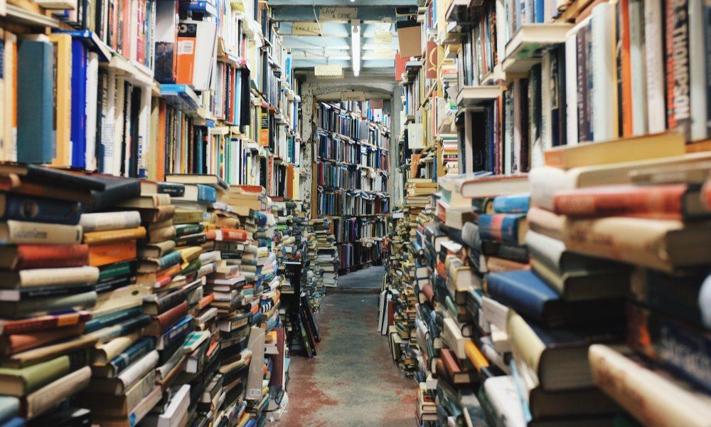 Gang in einem Gebäude mit Bücherstapeln zu beiden Seiten